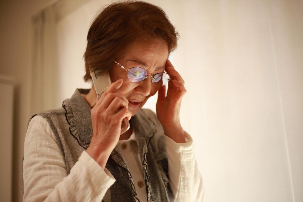 頭を抱える電話の女性