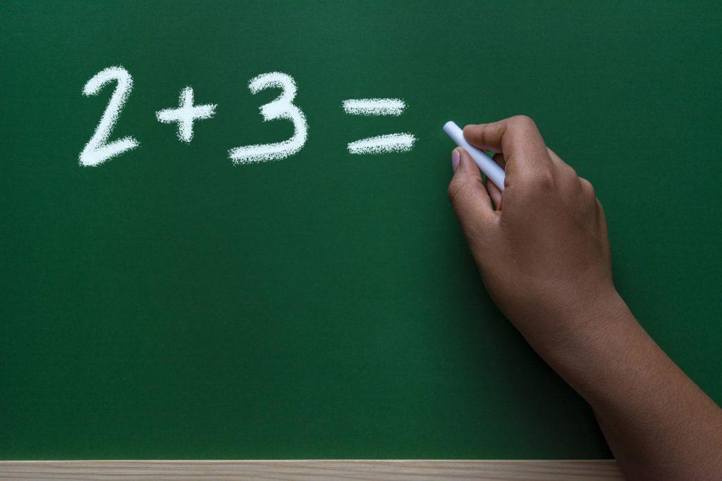 黒板に計算式を書く手